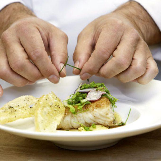 Chef Garnishing Fish Dish